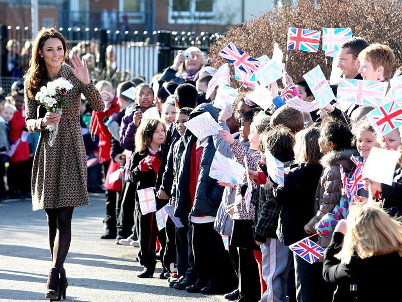 Britain's Catherine, the Duchess of Cambridge, waves as she arrives for an official visit to the Art Room facilities at Rose Hill Primary School in Oxford, central England. (AFP photo/Steve Parsons)
