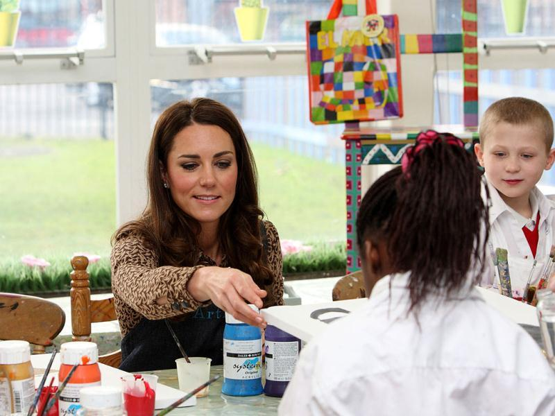 Britain's Catherine, the Duchess of Cambridge, helps school children with their painting during an official visit to the Art Room facilities at Rose Hill Primary School in Oxford, central Englan. (AFP photo/Steve Parsons)