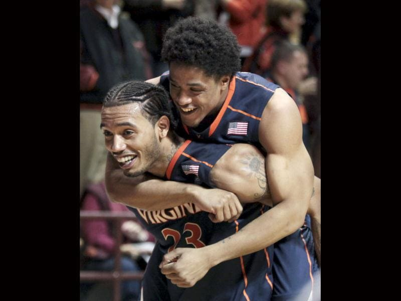 Virginiaís Jontel Evans rides on the back of Mike Scott (23) after Virginia defeated Virginia Tech 61-59 in an NCAA college basketball game in Blacksburg. AP/Matt Gentry