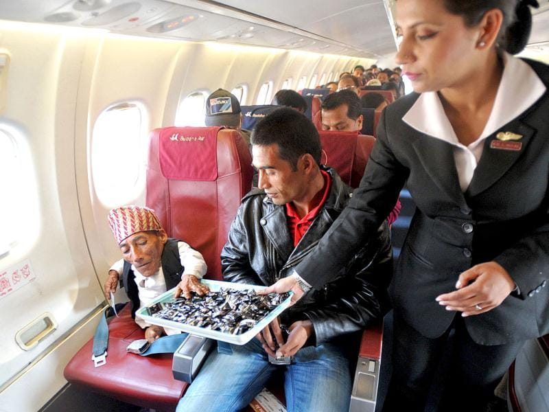 Chandra Bahadur Dangi, a 72-year-old Nepali who claims to be the world's shortest man at 56 centimetres (22 inches) in height, is offered refreshments by a Buddha Air flight attendant while on a flight to Kathmandu. Dangi embarked to the capital city as Guinness World Records experts are due to arrive in Nepal to measure a 72-year-old claiming to be the world's shortest man. AFP Photo/Prakash Mathema