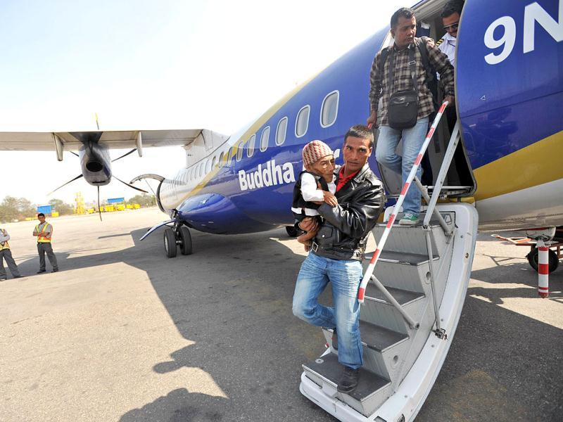 Chandra Bahadur Dangi, a 72-year-old Nepali who claims to be the world's shortest man at 56 centimetres (22 inches) in height, is carried by his nephew Doalk Dangi after arriving by flight in Kathmandu from Nepalgunj. Dangi embarked to the capital city as Guinness World Records experts are due to arrive in Nepal to measure a 72-year-old claiming to be the world's shortest man. AFP Photo/Prakash Mathema
