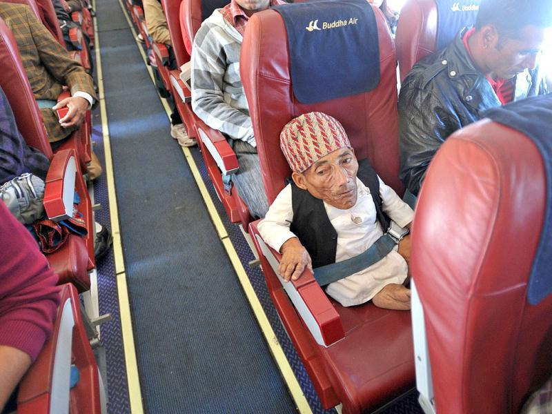 Chandra Bahadur Dangi, a 72-year-old Nepali who claims to be the world's shortest man at 56 centimetres (22 inches) in height, is seen in an aisle seat as the aircraft prepares for landing in Kathmandu. Dangi embarked to the capital city as Guinness World Records experts are due to arrive in Nepal to measure a 72-year-old claiming to be the world's shortest man. AFP Photo/Prakash Mathema