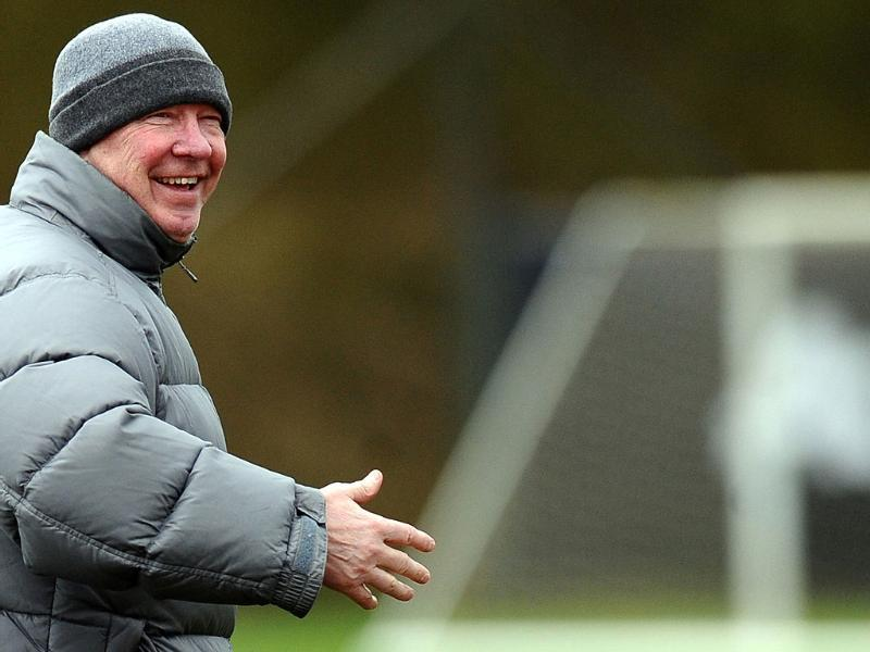 Manchester United manager Alex Ferguson laughs during a training session in Manchester. AFP photo/Paul Ellis