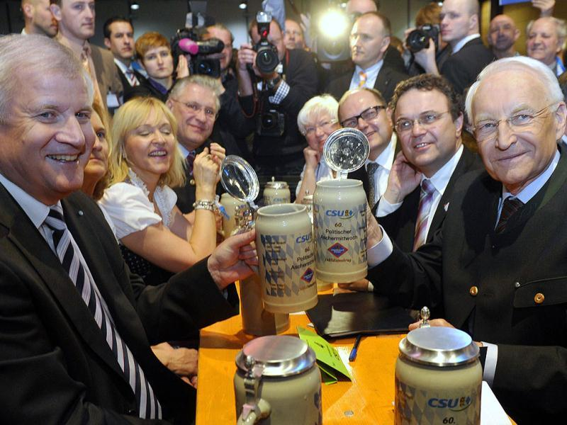 Bavarian state governor and head of German Christian Social Union (CSU) Horst Seehofer (L) and former Bavarian state governor Edmund Stoiber (R) hold up their beer mugs at the party's traditional Ash Wednesday rally in Passau, southern Germany. (AFP Photo/Thomas Kienzle)