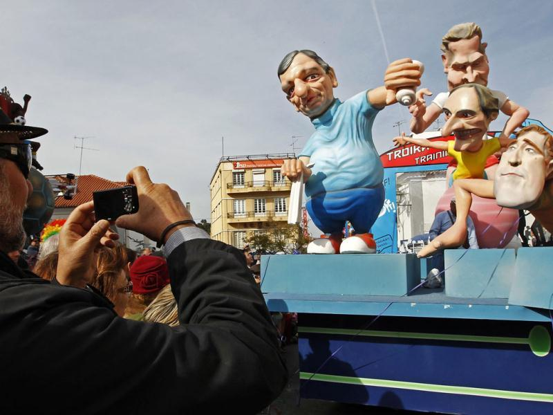 A man takes a photo of a carnival float depicting European Commission President Jose Manuel Barroso (L) giving water to Portuguese Prime Minister Passos Coelho (R), alongside Foreign Minister Paulo Portas and IMF delegation chief Paul Thomson (back), at the Torres Vedras parade. The Portuguese have mostly quietly accepted reforms in the labour market, soaring unemployment and cuts to welfare to rein in their debt mountain - but calls to cancel the centuries-old tradition of carnival went a step too far.The government tried, in the name of austerity imposed by international lenders, to force the end of Tuesday's public holiday but the country effectively shut down all the same as the Portuguese refused to go without their pre-Lent festival. REUTERS/Jose Manuel Ribeiro