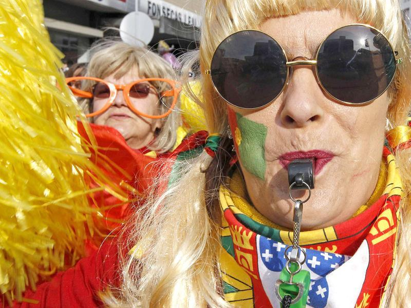 A carnival reveller with an image of a Portuguese national flag printed on her face, whistles at the Torres Vedras parade. The Portuguese have mostly quietly accepted reforms in the labour market, soaring unemployment and cuts to welfare to rein in their debt mountain - but calls to cancel the centuries-old tradition of carnival went a step too far. The government tried, in the name of austerity imposed by international lenders, to force the end of Tuesday's public holiday but the country effectively shut down all the same as the Portuguese refused to go without their pre-Lent festival. REUTERS/Jose Manuel Ribeiro