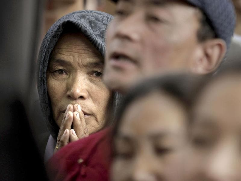 An exiled Tibetan woman prays as others shout slogans against the Chinese government outside the Chinese Embassy on the first day of the Tibetan New Year, in New Delhi. AP Photo/ Manish Swarup