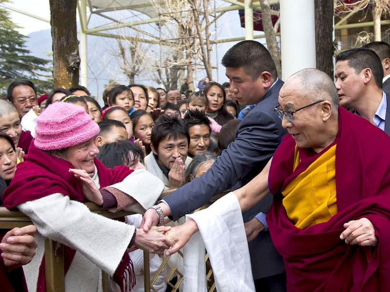 Tibetan spiritual leader the Dalai Lama (R) greets a devotee as he leaves after leading a prayer session on the first day of the Tibetan New Year at the Tsuglakhang temple in Dharmsala. AP Photo/Ashwini Bhatia