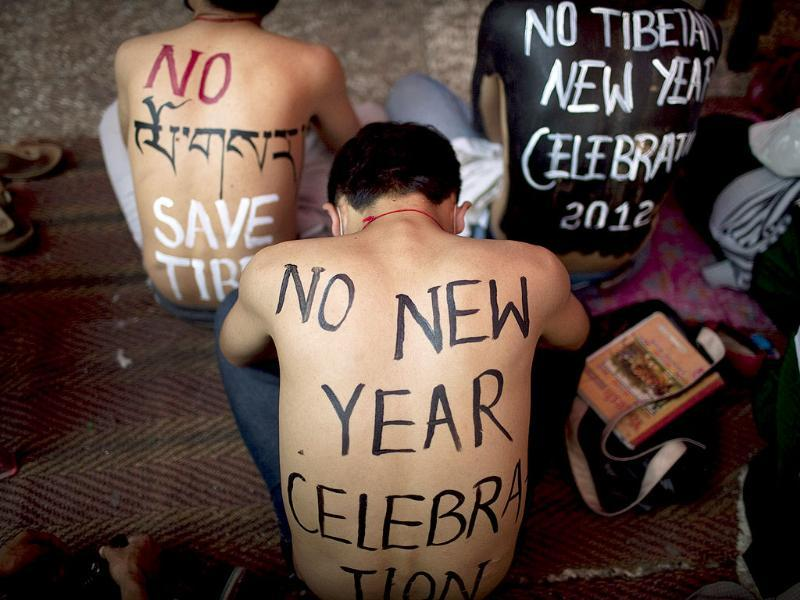 Exiled Tibetan students have slogans painted on their bodies as they take part in a day-long hunger strike on the first day of the Tibetan New Year, at a Buddhist temple in New Delhi. AP Photo/Kevin Frayer