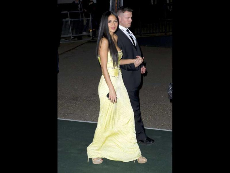 US singer Nicole Scherzinger is escorted by a member of security to the Brit Awards after party.