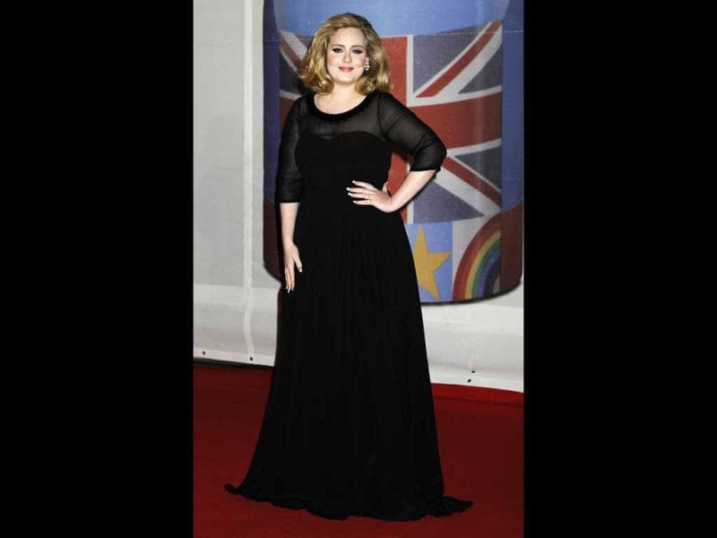 Adele in a black dress poses for a smile.