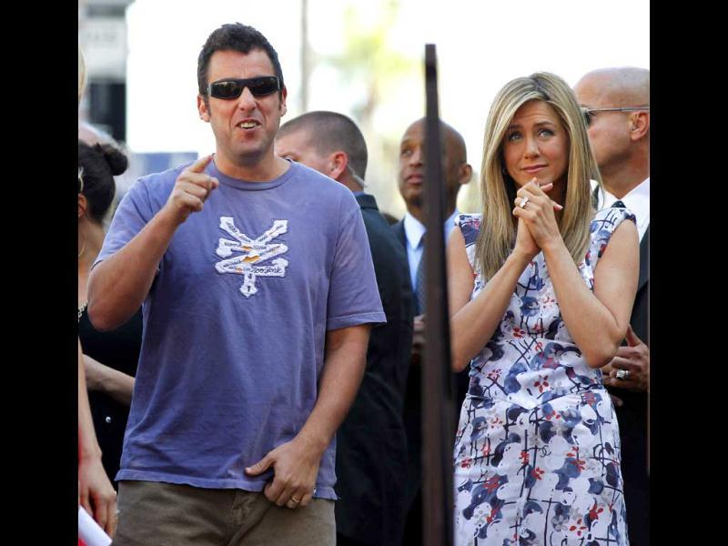 Aniston stands next to actor Adam Sandler before unveiling her star on the Walk of Fame.