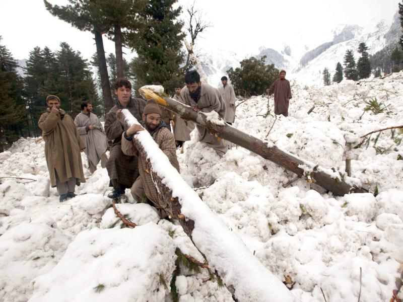 Kashmiri villagers remove fallen trees as they search for belongings at the site where their homes stood, now buried in snow after an avalanche in Ramwari, some 70 kilometers (44 miles) northeast of Srinagar. Heavy snowfall across Kashmir valley has prompted authorities to issue an avalanche warning for most areas lying close to the mountains, according to a news agency. Avalanches and landslides are common in the disputed Himalayan region. AP Photo/ Dar Yasin