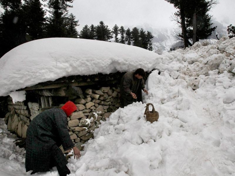 Residents clearing snow after an avalanche at Ramwari village near Gund in Ganderbal district on Thursday. Sixteen soldiers were killed, 4 injured and three more are missing after avalanches buried military camps in Sonamarg and Ganderbal areas. PTI Photo by S Irfan