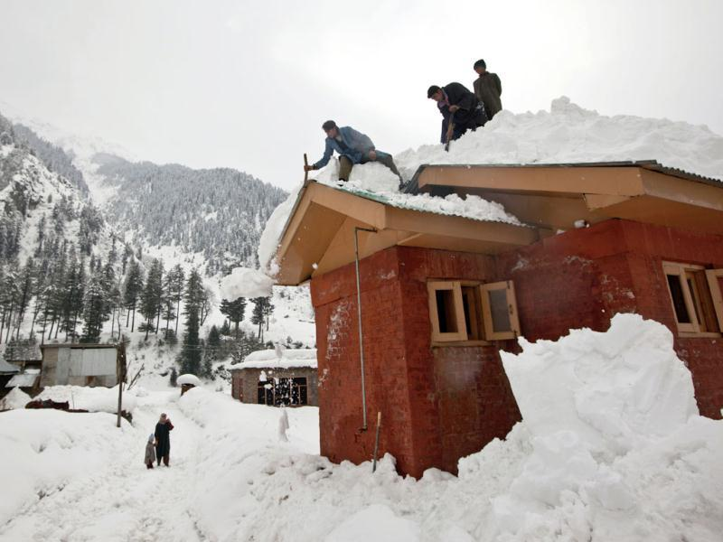 Kashmiri boys clear snow from the roof of a house in Gagangeri, some 80 kilometers (50 miles) northeast of Srinagar. Heavy snowfall across Kashmir valley has prompted authorities to issue an avalanche warning for most areas lying close to the mountains, according to a news agency. Avalanches and landslides are common in the disputed Himalayan region. AP Photo/ Dar Yasin