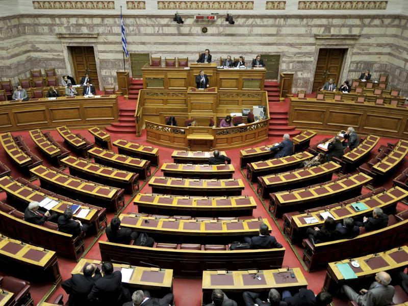 Greek finance minister Evangelos Venizelos (C) talks during a parliament debate in Athens. Greek parliament went into overdrive to approve necessary laws needed for an unprecedented debt write down with private creditors, a condition for a new eurozone bailout to avert a looming default. Parliamentary committees began debating a pressing law setting up rules and procedures for debt restructuring with private creditors (PSI) which is expected to be voted later in the day. AFP PHOTO/ LOUISA GOULIAMAKI