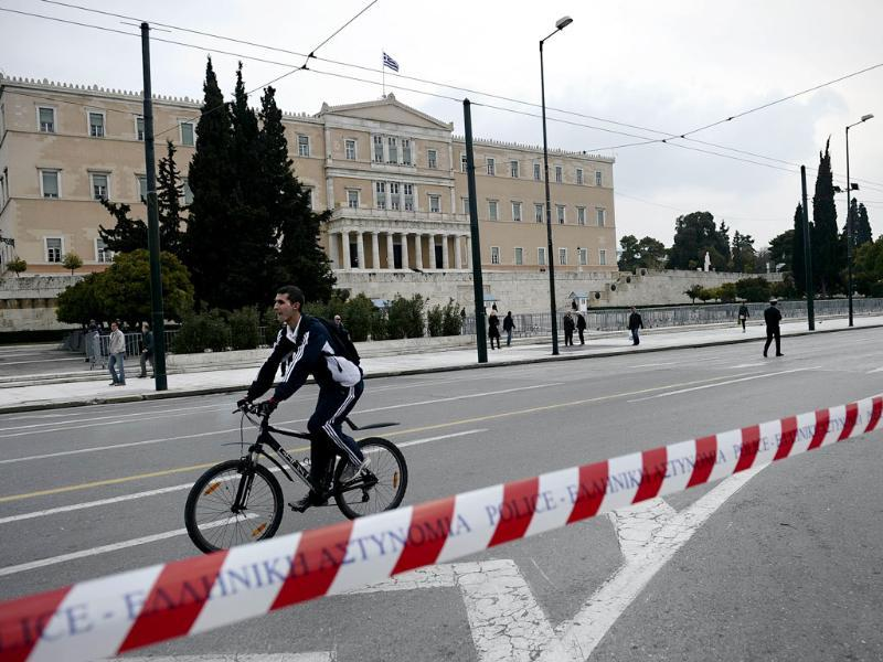 A man rides his bicycle in front of the Greek parliament during a demonstration against the government's austerity measures in central Athens as Greek parliament met to approve laws needed for a historic debt write down with private creditors, a key condition for a new eurozone bailout designed to avoid default. AFP PHOTO / ARIS MESSINIS