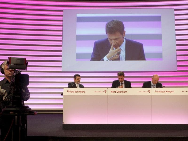 Deutsche Telekom CEO Rene Obermann is seen on a large screen during the annual news conference in Bonn February. Deutsche Telekom suffered a net loss of 1.3 billion euros ($1.7 billion) in the fourth quarter as a cash payment for the collapsed T-Mobile USA deal failed to offset accounting charges on its activities in the United States and Greece. REUTERS/Ina Fassbender