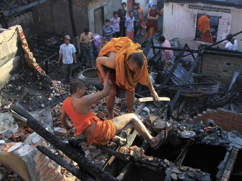 A Cambodian Buddhist monk, loses balance as he collects some scraps after their houses caught fire, in a Buddhist pagoda, Wat Saravoan Techor, in Phnom Penh, Cambodia. At least five houses burned down. (AP Photo)
