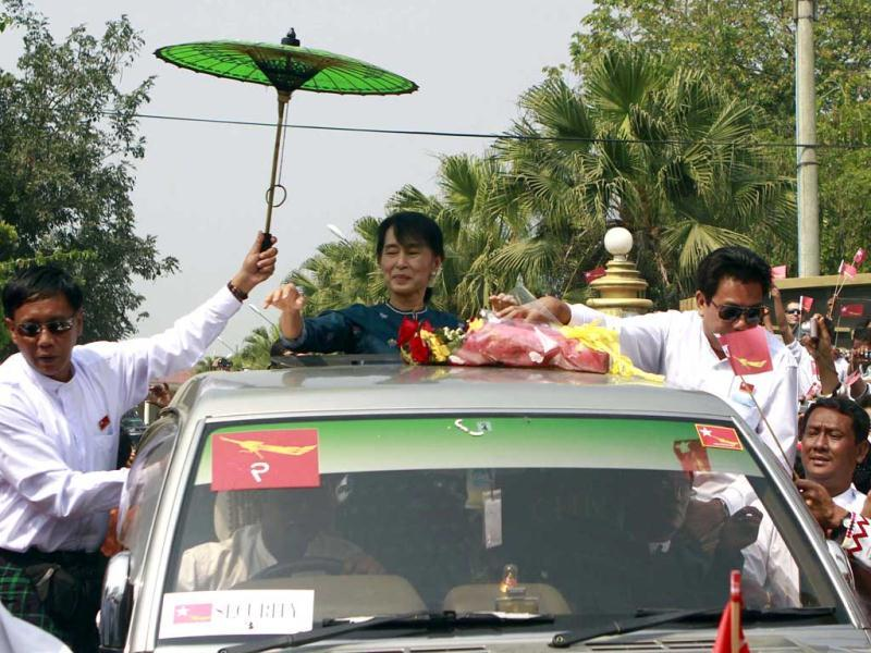 Myanmar pro-democracy icon Aung San Suu Kyi greets supporters from her vehicle on her arrival at Myitkyina, Kachin State, northern Myanmar. (AP Photo)