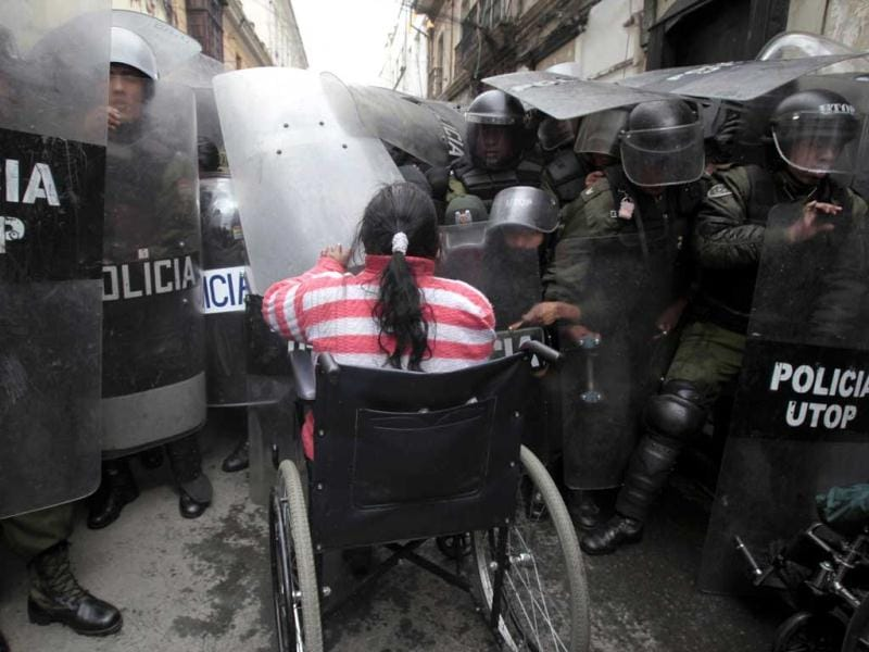 A physically disabled woman on her wheelchair clashes with riot police in La Paz. Hundreds of physically disabled people arrived in La Paz after completing a protest march of some 1600km over a hundred days to demand that Bolivia's government offer support in the form of 3000 bolivianos ($434) payment to each physically disabled Bolivian, according to local media. (Reuters)