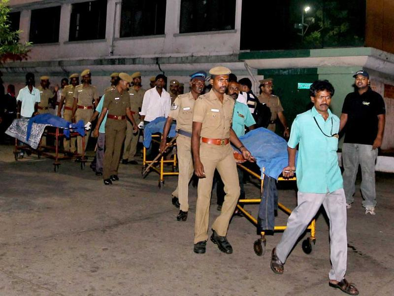 Police take the bodies of bank robbers to a government hospital mortuary after an encounter near Velachery in Chennai. PTI/R Senthil Kumar