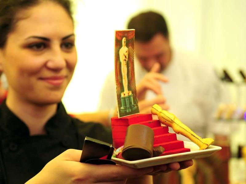 A waitress displays the Chocolate Staircase, a chocolate mousse desert to be eaten wearing 3D glasses to see image on desert.