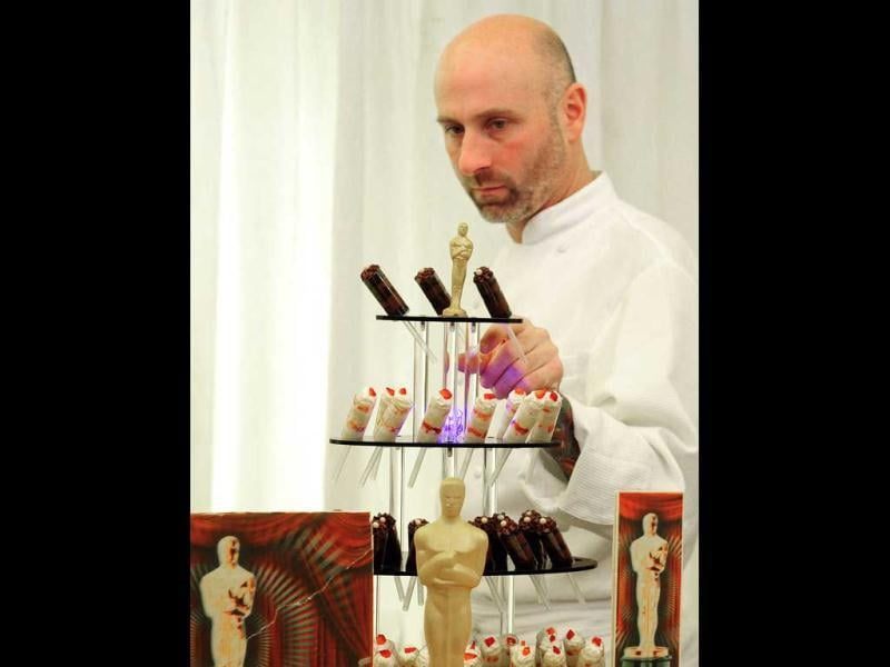 A chef prepares a display of deserts that include Gold chocolate Oscars.