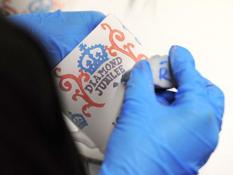 A worker paints diamond jubilee mugs at the Emma Bridgewater pottery in Hanley, Stoke on Trent, England as part of a collection to celebrate the queen's 60-year reign. The Diamond Jubilee range will feature both hand decorated spongeware patterns and lithographed prints on celebratory mugs, bowls, plates, teapots and a ceramic crown emblazoned with the slogans 'Sixty Years a Queen' and 'Steadfast and True. AFP PHOTO / Andrew Yates