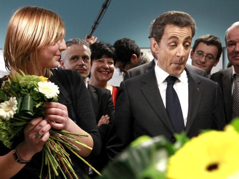 Nicolas Sarkozy (R), France's President and UMP party candidate in the French 2012 presidential election, reacts as he stands with an apprentice florist at a trade school in Tourcoing during a campaign trip. Reuters/Pascal Rossignol