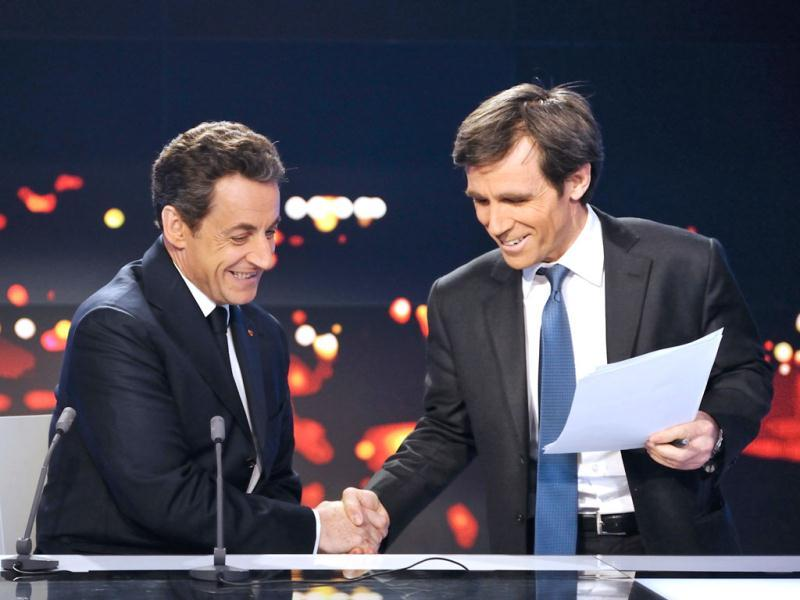 Nicolas Sarkozy (L), France's President and the UMP candidate for the 2012 presidential election, shakes hands with journalist David Pujadas at the France 2 Television studios on their prime time evening news programme in Paris. Reuters/Eric Feferberg/Pool