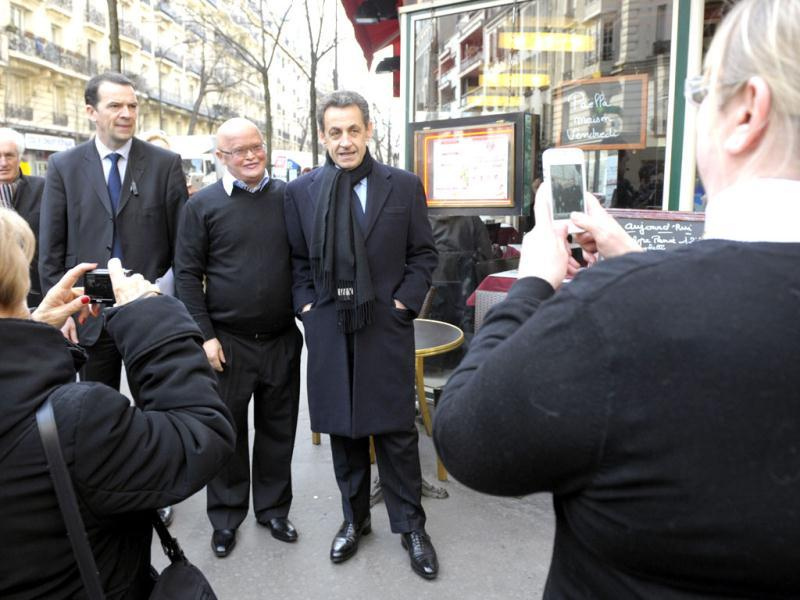 France's President and UMP party candidate for the 2012 French presidential elections Nicolas Sarkozy (R) poses in the street for a souvenir photo as he arrives for a meeting with UMP deputies in Paris. Reuters/Philippe Wojazer