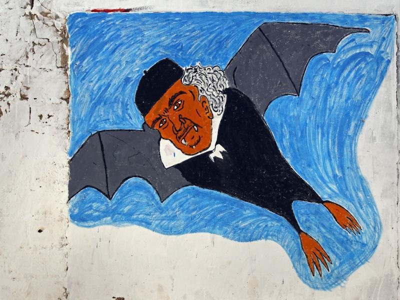 Picture depicting Muammar Gaddafi as bat is seen painted on wall near main square in town of Zintan in Libya's Western Mountains. (Reuters/Bob Strong)