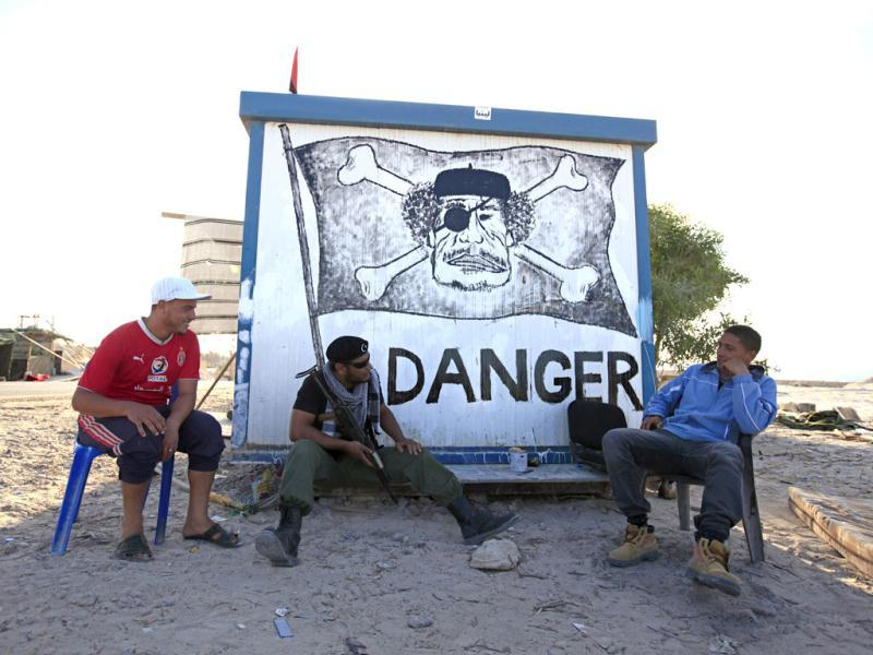 Libyan rebel fighters sit by a caricature of Muammar Gaddafi at a checkpoint west of the rebel-held city of Misrata. (Reuters/Zohra Bensemra)