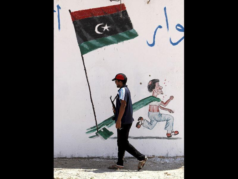 A rebel fighter walks past a graffiti of Muammar Gaddafi on a checkpoint building controlled by rebels in Zintan. (Reuters/Ammar Awad)
