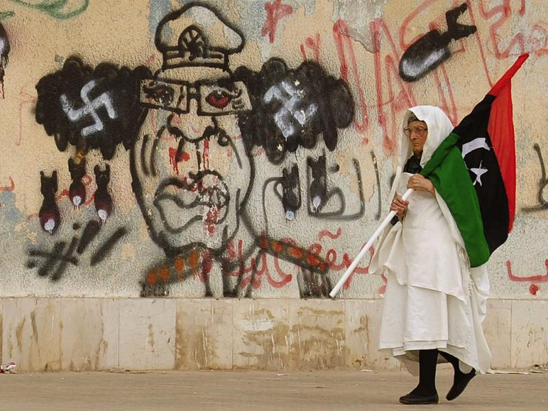 A Libyan woman holding a Kingdom of Libya flag walks past a caricature of Muammar Gaddafi near the court house in Benghazi. (Reuters/Esam Al-Fetori)