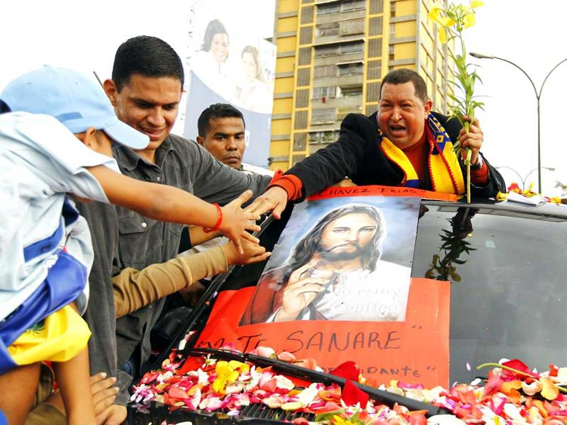 Venezuela President Hugo Chavez greets supporters on his way to the airport, before his departure to Cuba in Caracas. Reuters/Jorge Silva