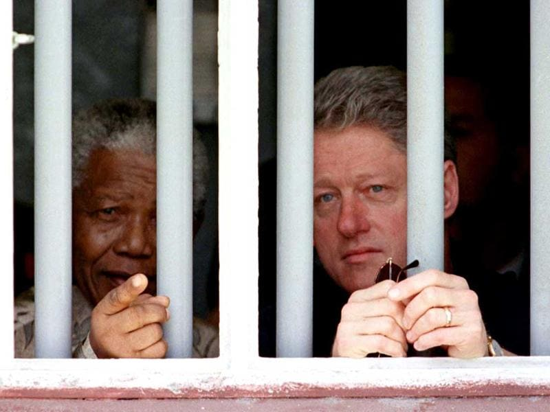 Former US president Bill Clinton and former South African president Nelson Mandela peer through the bars of the cell in which Mandela spent 17 years while incarcerated by the former South African government. (Reuters file photo)