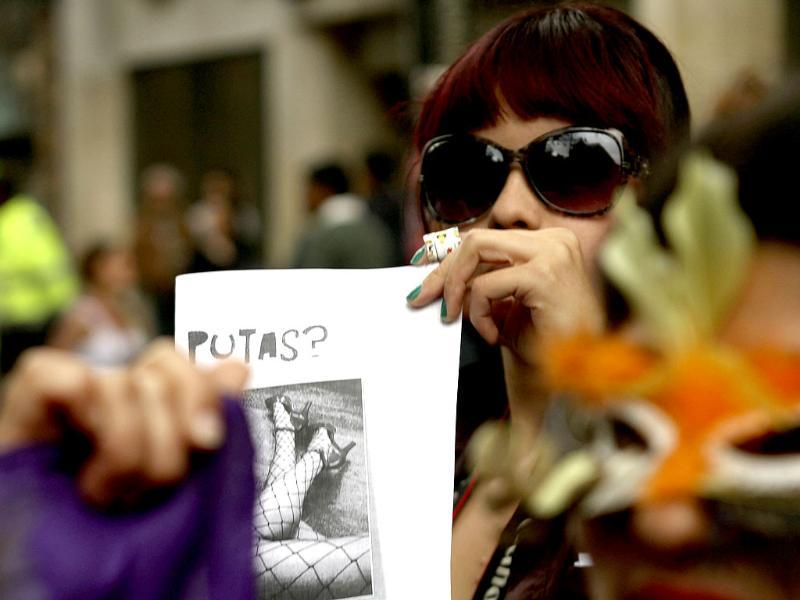 A woman holds a poster with the word Whore on it during a 'March of the whores' held to protest against discrimination and violence against women in Bogota. Reuters/Fredy Builes