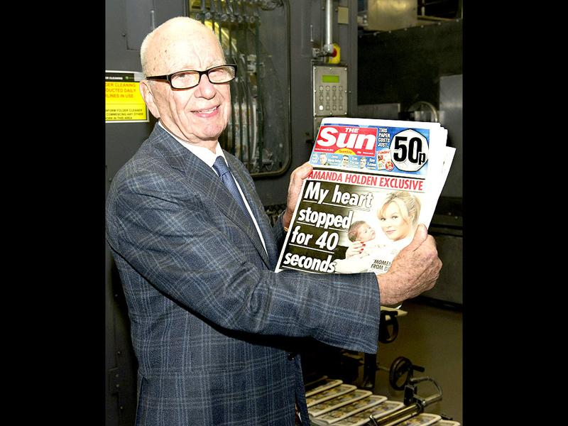A handout photo provided by News International Group Ltd shows the chairman and chief executive officer of News Corporation, Rupert Murdoch, holding the first edition of The Sun on Sunday as it came off the presses at Broxbourne, outside London. (AFP PHOTO / News International Group Ltd)