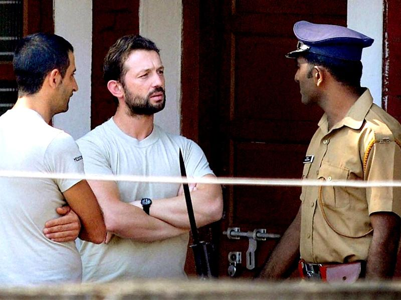A policeman with the Members of the navy security team of Italian vessel Enrica Lexie, Salvatore Girone (C) and Latorre Massimiliano, who were involved in the killing of two Indian fishermen, at a government guest house in Kochi. PTI Photo