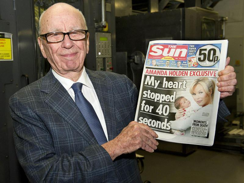 A handout photo provided by News International Group Ltd shows the chairman and CEO of News Corporation, Rupert Murdoch, holding the first edition of The Sun on Sunday as it came off the presses at Broxbourne, outside London. (AFP Photo)