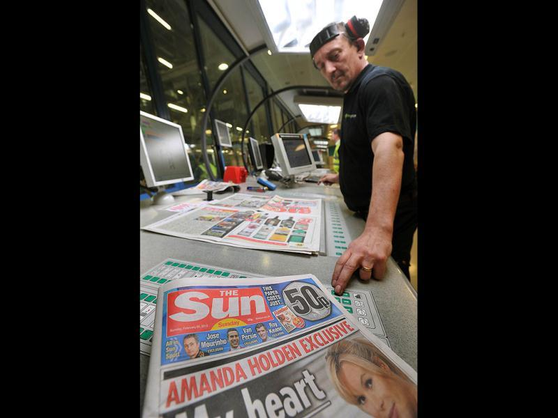 An employee checks copies of the new The Sun on Sunday at the News Printers plant in Broxbourne, outside London. Chairman and CEO of News Corporation, Rupert Murdoch, said he wanted the paper replacing the scandal-hit News of the World to sell over two million copies. (AFP Photo)
