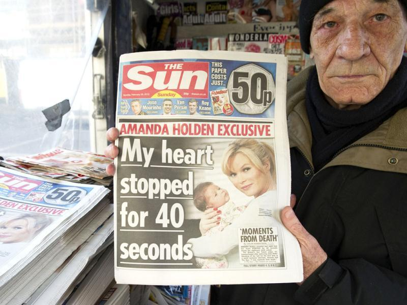 A person holds up Sunday's edition of the new British Newspaper 'The Sun on Sunday'. Rupert Murdoch's Sun on Sunday tabloid rolled off the presses for the first time, with a pledge that the paper replacing the scandal-hit News of the World would abide by ethical standards. (AFP photo/Miguel Medina)