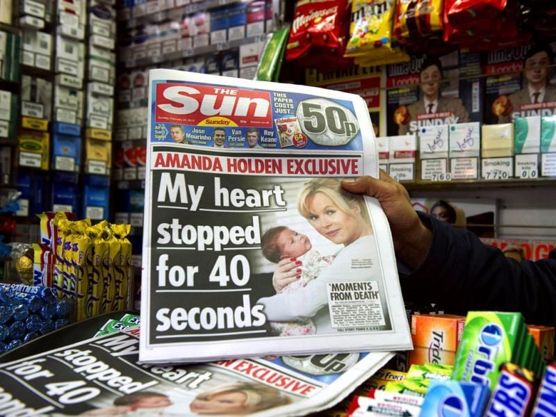 A person holds up Sunday's edition of the new British Newspaper 'The Sun on Sunday' in London. Rupert Murdoch's Sun on Sunday tabloid rolled off the presses for the first time, with a pledge that the paper replacing the scandal-hit News of the World would abide by ethical standards. (AFP photo/Miguel Medina)