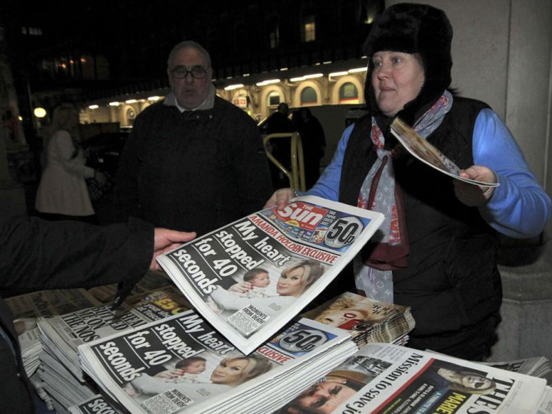 A customer buys the first edition of 'The Sun on Sunday' for sale at Charring Cross station in London. (Reuters/Olivia Harris)