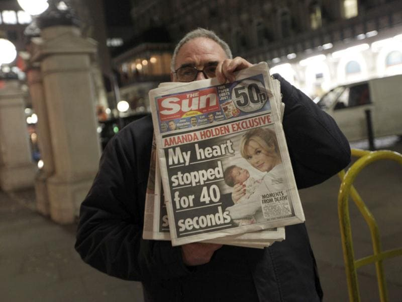 A newsagent poses with copies of the newly-published 'The Sun on Sunday' weekly tabloid, in central London. (AP Photo/Lefteris Pitarakis)