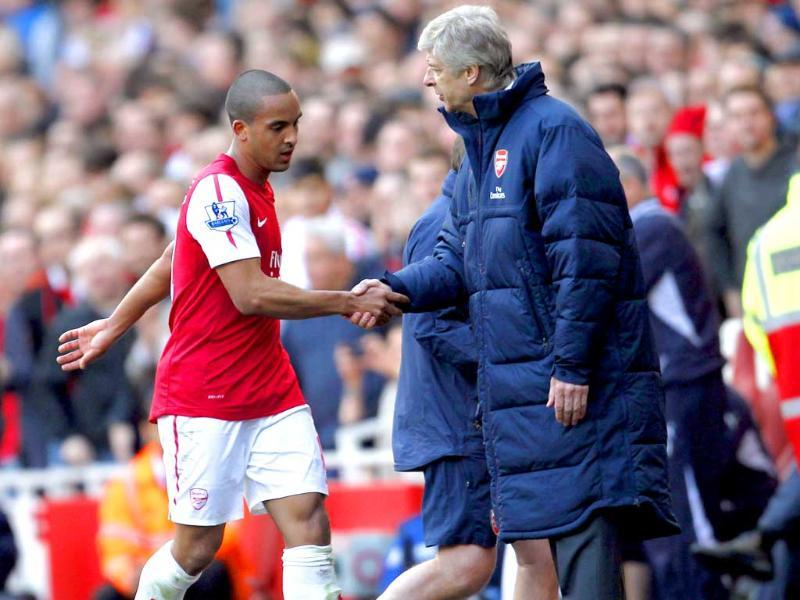 Arsenal manager Arsene Wenger (R) shakes hands with Theo Walcott (L) after he was substituted during an English Premier League football match against Tottenham Hotspur at The Emirates Stadium in London. AFP Photo/Ian Kington