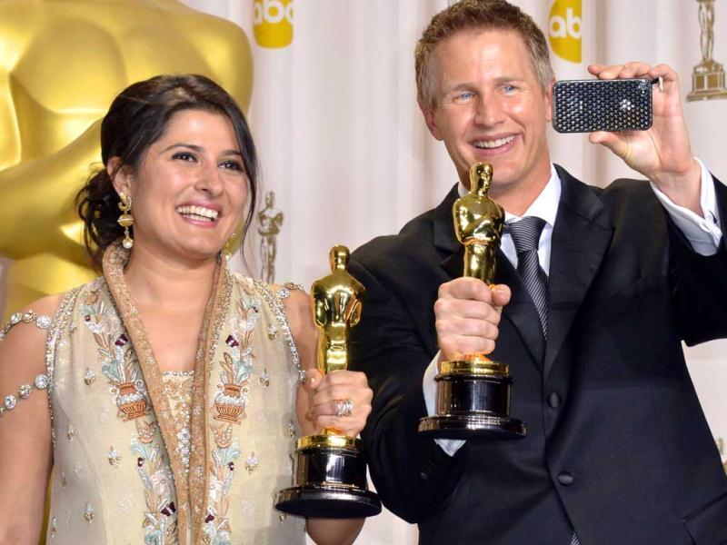 Winners for Best Documentary Shor Saving Face, Daniel Junge and Sharmeen Obaid-Chinoy poses with the trophy in the press room at the 84th Annual Academy Awards. (AFP)