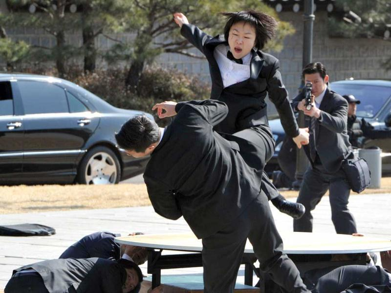 A female presidential body guard shows off her martial art skills during an anti-terror drill at the president's residence, showcasing security preparations for an upcoming nuclear summit in Seoul. AFP Photo/Kim Jae-Hwan.